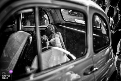 Picture of a bride reflected in the glass of a waiting automobile by a Donnas AO wedding photographer