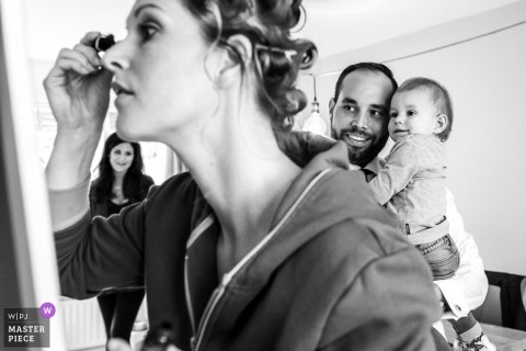 Noord Brabant wedding photograph of the bride applying mascara to her eyes as a woman man and baby look on