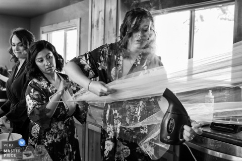 South Lake Tahoe, Nevada bridal party helps with steaming of bride's veil before ceremony