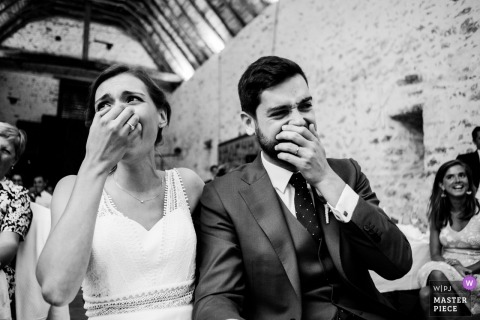 Bride and groom cover faces as they laugh at Chateau de la Fresnay, Angers