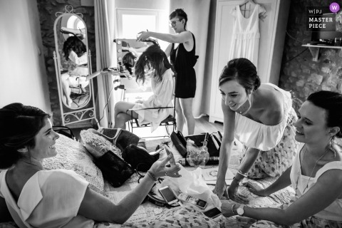 Montpellier, FRANCE documentary wedding photo of the bride having her hair styled as bridesmaids look at a phone on the bed