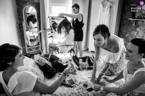Montpellier, FRANCJA dokumentalna fotografia ślubna panny młodej o fryzurach wyglądających jak druhny na telefon na łóżku