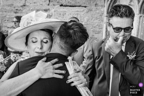 Montpellier, FRANCE wedding photo of a groom hugging a guest | wedding photograph in black-and-white
