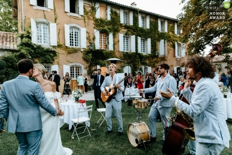 Provence - France wedding photojournalism image of a couple dancing and kissing during their outdoor reception with a live band Close by