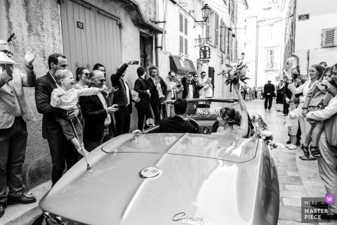 Ślubna sesja z parą Saint Tropez odjeżdżającą w kabriolecie Corvette, w dół wąską ulicą z gośćmi