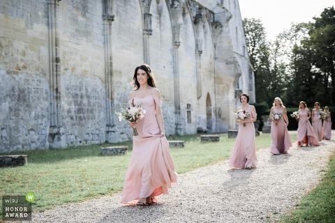 Dokumentarisches Hochzeitsfoto Frankreichs der Zeremonie mit den Brautjungfern, die hinunter Kiesweg gehen