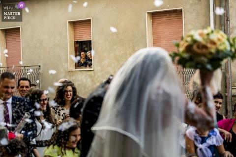 Reggio Calabria documentary wedding photo of bride and groom under flower petal shower