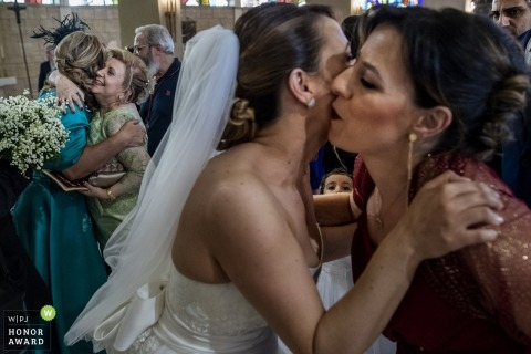 Reggio Calabria wedding photo of bride kissing relatives at the church   wedding photography