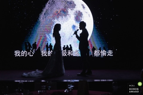 Wedding shoot with Taiwan couple with microphone and large screen behind them on stage