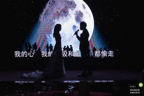 Hochzeitsshooting mit Taiwan-Paaren mit Mikrofon und großem Bildschirm hinter ihnen auf der Bühne
