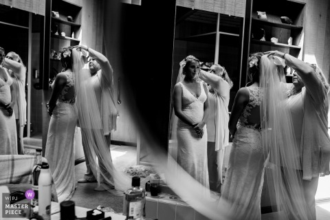 Wedding pictures of bride putting on veil in many mirrors by Sacramento photographer