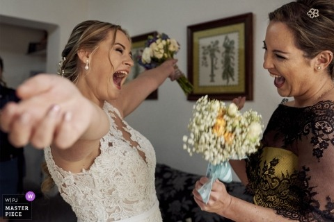 Spain wedding photograph of a very excited bride about to hug a bridesmaid with her arms wide open