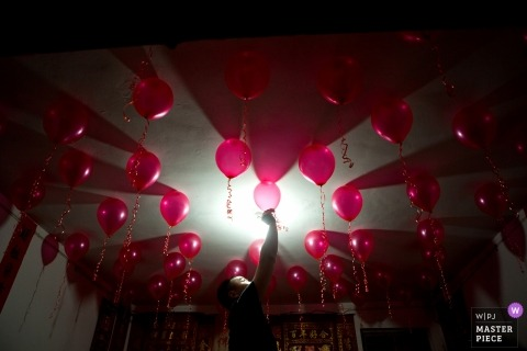 Wedding photojournalism in Fujian of many red balloons decorating the ceiling