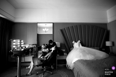 Documentary wedding photograph in Fujian of a bride receiving facial treatment and makeup with her dress lying on the bed