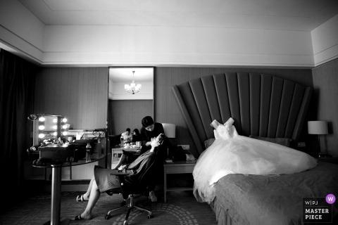 Dokumentalna ślubna fotografia w Fujian panna młoda otrzymywa twarzowego traktowanie i makeup z jej suknią kłama na łóżku