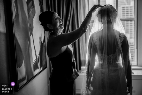 Chicago documentary wedding photo of a bride standing near a window in the hotel having her veil adjusted by a friend
