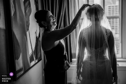 Chicagowska dokumentalna fotografia ślubna panny młodej stojącej przy oknie w hotelu, mająca dostosowaną przez przyjaciółkę zasłonę