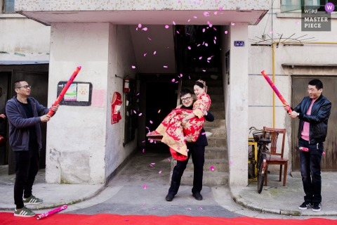 Zhejiang wedding shoot with a groom carrying the bride as two men ignite confetti cannons