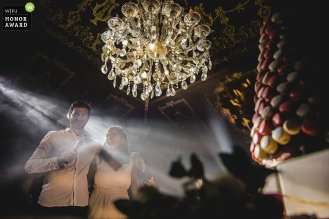 Picture of a couple giving speeches using a microphone at the reception by a top Paris wedding photographer