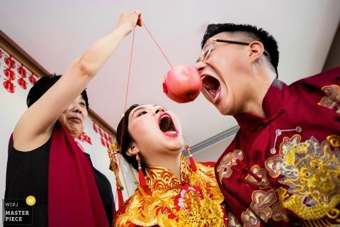 Ślubna strzelanina z parą Szanghaju biorąca ugryzienia od jabłka wiszącego na sznurku