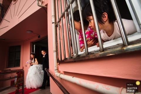 Szanghaj ślubny fotoreportaż obraz panny młodej opuszczającej swój dom, gdy małe dzieci patrzą z okna