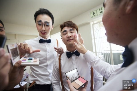 Singapore documentary wedding photo of groomsmen Looking good putting makeup on each other