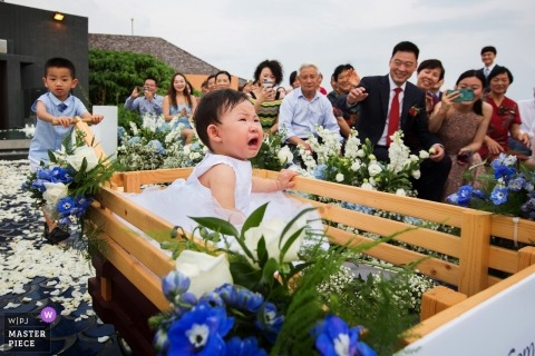 Huizhou wedding photograph of a boy and girl using a wagon down the aisle of the ceremony outside
