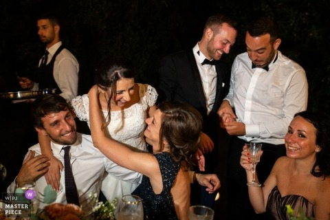 Rome wedding photojournalism image of a couple hugging and interacting with reception guests