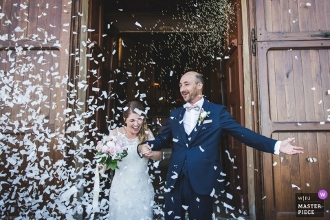Picture of a couple with confetti at the church by a top Piedmont photographer - Langhe wedding photographer