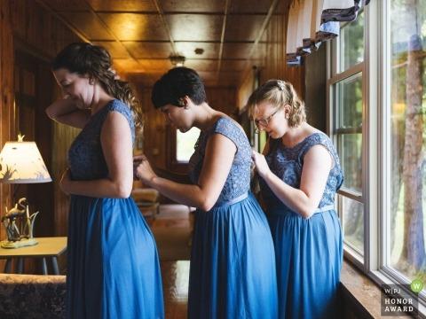 Documentaire huwelijksfoto van bruidsmeisjes die elkaars jurken repareren bij Alamoosook Lakeside Inn in Orland, ME