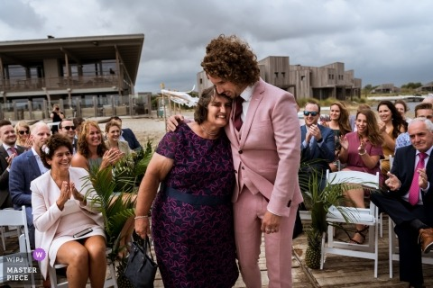 Ślub dokumentalny Rockanje-Holland pana młodego przytulającego matkę na początku ceremonii plenerowej
