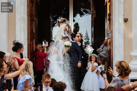 Portofino wedding photojournalism image of a couple getting dumped on with bag of rice after ceremony
