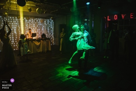 UK Wedding Photography | A couple dancing under a green light in a darkened room at Islington Metalworks