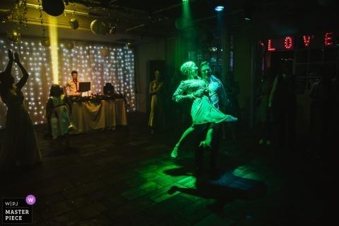 UK Hochzeitsfotografie | Ein Paar tanzt unter grünem Licht in einem dunklen Raum in Islington Metalworks