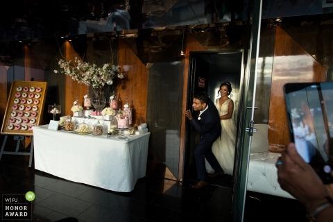 Picture of a couple entering reception venue near the cake - Melbourne wedding photographer