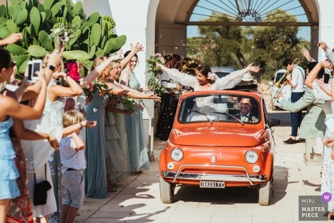 A couple drive through a line of wedding guests throwing confetti in a vintage Fiat car at Masseria Potenti in Italy