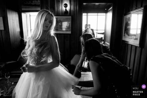 Chamonix wedding photo out of bride having her dress adjusted by some friends | wedding photography for Lyon
