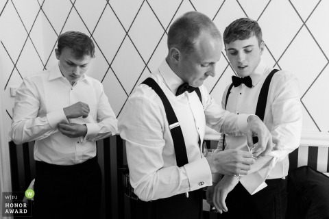 Wedding photo from the French Riviera  of the groom and groomsmen adjusting their cufflinks