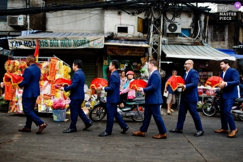 Wedding photojournalism at Ho Chi Minh of groomsmen walking single file down a Vietnam street