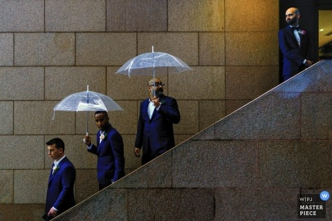 Documentary wedding photography of men coming down stairs in the rain with umbrellas at Ho Chi Minh
