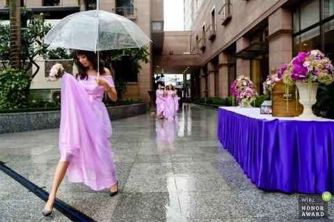 Ho Chi Minh-documentaire huwelijksfoto van een bruidsmeisje in een roze kleding die haar boeket en een paraplu houden aangezien zij op de natte stoep loopt