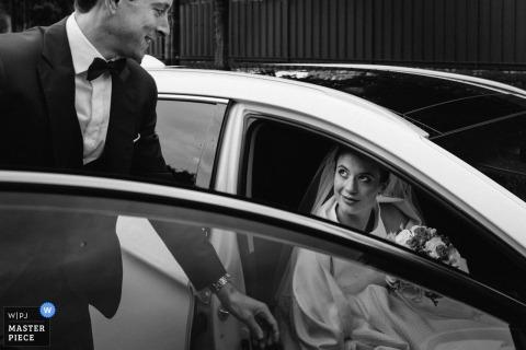 Pan młody Le Chesnay pomaga swojej narzeczonej z samochodu podczas ślubu