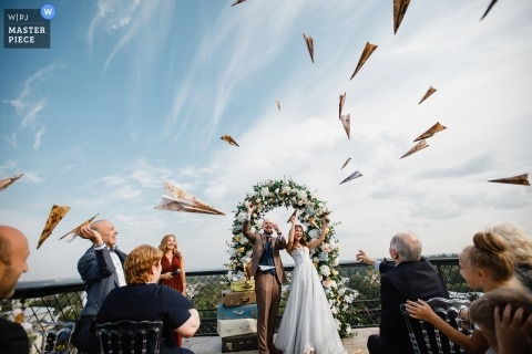 Documentary wedding photograph of guest throwing paper airplanes during ceremony in Russia, St. Petersburg