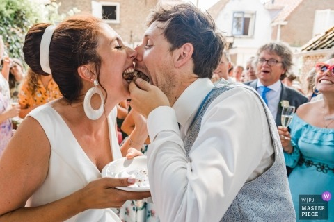 Zuid Holland wedding image with a couple shoving cake into their mouths together