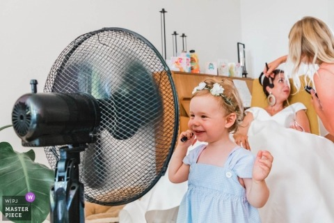 Wedding pictures of a young flower girl cooling off with the fan as the bride has make applied - Zuid Holland photographer