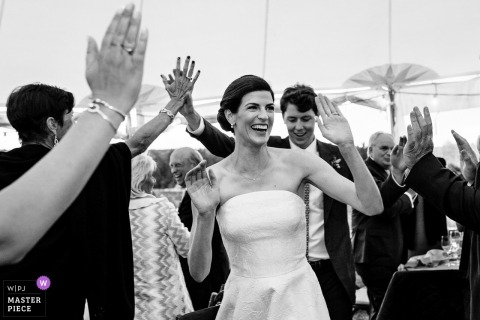 Blue Hill, Maine wedding photojournalism image of a bride and groom giving guests high-fives