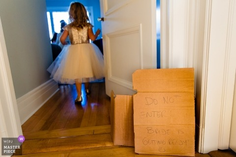 Documentary wedding photography at Blue Hill, Maine - a young flower girl passes A do not enter sign