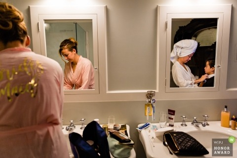 Blue Hill, Maine documentary wedding photo of bridesmaids and the bride getting ready in the bathroom with a young ringbearer