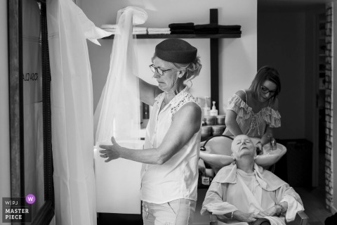 Ślubna sesja zdjęciowa w Nantes - kobieta sprawdza welon panny młodej i sukienkę, jak inna ma umyte włosy
