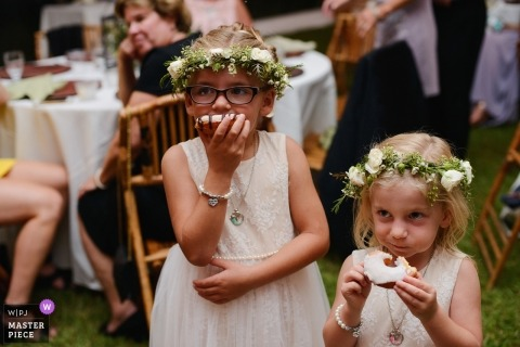 Corolla, NC wedding photograph of flower girls eating donuts